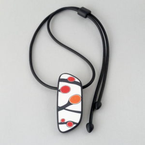 Handmade pendant showing a graphic flower bud motif in orange tones, on a white background with a charcoal border. It is approximately 2.6 cm wide and 6.4 cm long and hangs on a black adjustable cord.