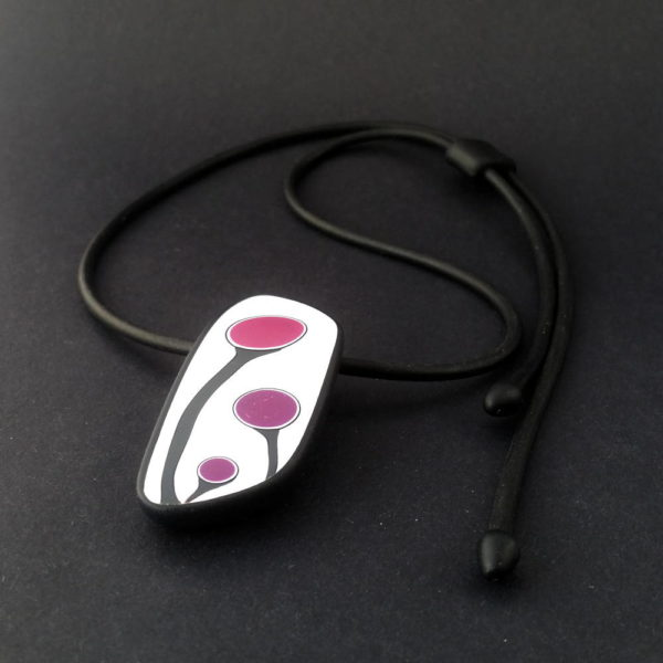 Handmade shield shaped necklace featuring an abstract flower bud motif in plum on a white background, with charcoal border. It is approximately 2.6 cm wide and 6. long and hangs on a black adjustable cord.