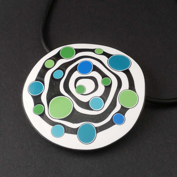 Large handmade pendant with organically-shaped concentric black and white circles, and irregular dots of bright blue and green. It is approximately 6.6cm in diameter and hangs on a black adjustable cord.