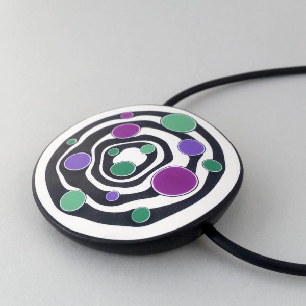 Large handmade pendant with organically shaped concentric black & white circles, and irregular dots of purple, green and magenta. It's approximately 6.6cm in diameter and hangs on a black adjustable cord.