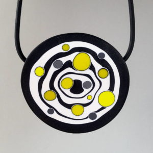 Large handmade pendant with organically-shaped concentric black and white circles, and irregular dots of bright yellow. It is approximately 6.6cm in diameter and hangs on a black adjustable cord.