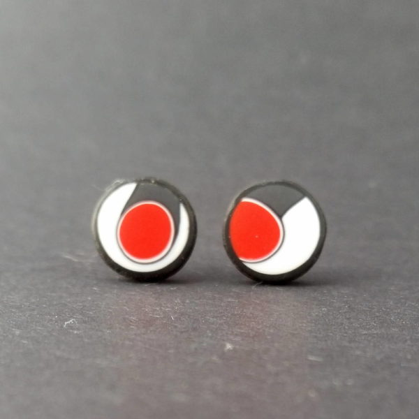 Handmade stud earrings with asymmetrical abstract flower bud pattern in red, on a white background with a charcoal border. Surgical stainless steel posts.