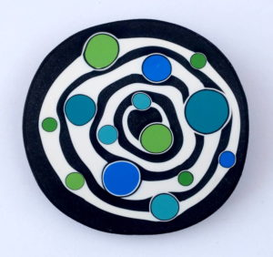 Handmade large bead with concentric black and white circles, and bright blue and green irregular dots.