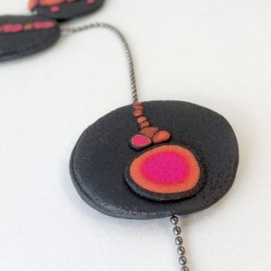 Handmade long necklace with individually crafted flat beads in vibrant orange and magenta on a black, textured background. Length approx. 120cm.