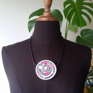 Large handmade pendant with organically-shaped concentric black and white circles, and irregular dots in various pinks. It is approximately 6.6cm in diameter and hangs on a black adjustable cord.