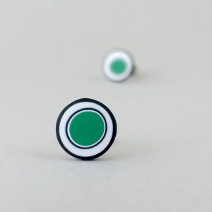 Handmade stud earrings with organic circles of emerald green on a white background with a black border.