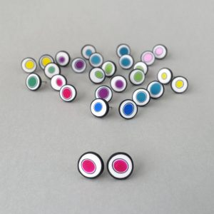 Handmade stud earrings with organic circles of magenta on a white background with a black border.