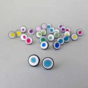 Handmade stud earrings with organic circles of turquoise on a white background with a black border.