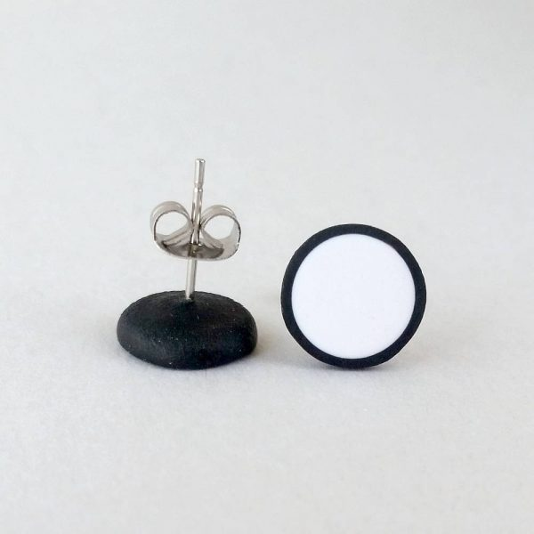 Handmade stud earrings in pure white with a black border.