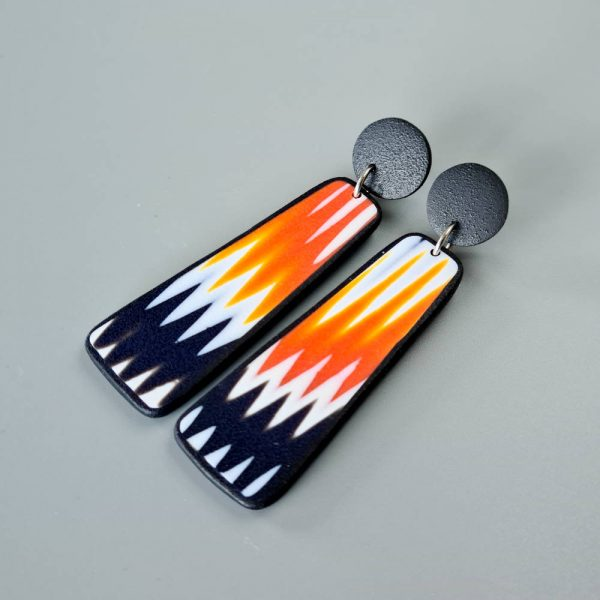 Handmade dangle earrings with zigzag pattern in black, white and orange.
